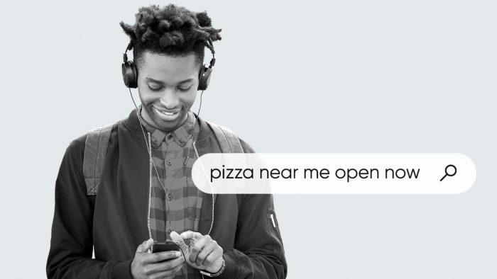 homme portant un casque et utilisant un téléphone portable pour chercher une «pizzeria à proximité» ouverte
